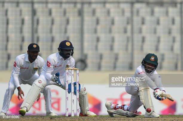 Bangladesh batsman Mominul Haque plays a shot as Sri Lanka's wicketkeeper Niroshan Dickwella and Dimuth Karunaratne look on during the third day of...
