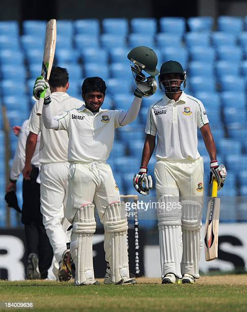 Bangladesh batsman Mominul Haque reacts after scoring a century as his teammate Anamul Haque looks on during the third day of the first cricket Test...