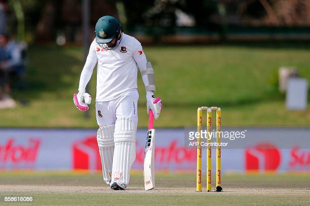 Bangladesh batsman Mushfiqur Rahim leaves the ground after South Africa fielder Temba Bavuma caught him out during the second day of the second Test...