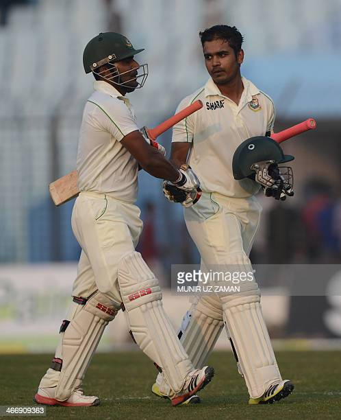 Bangladesh batsman Shamsur Rahman shakes hands with teammate Imrul Kayes as they leave the field after the second day of the second Test match...