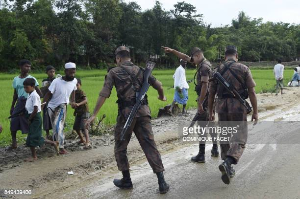 TOPSHOT Bangladesh Border Guard attempts to clear Rohingya Muslim refugees off a road near Balukhali refugee camp near the Bangladehsi district of...