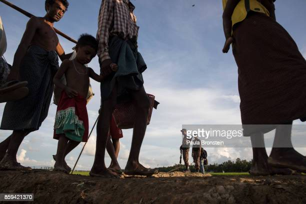 Bangladesh border guard stands by as thousands of Rohingya refugees fleeing from Myanmar walk along a muddy rice field after crossing the border in...