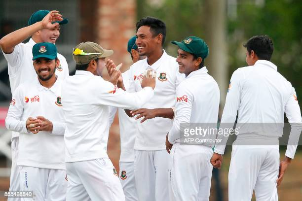 Bangladesh bowler Mustafizur Rahman celebrates with teammates after his dismissal of unseen South African batsman Dean Elgar during the second day of...