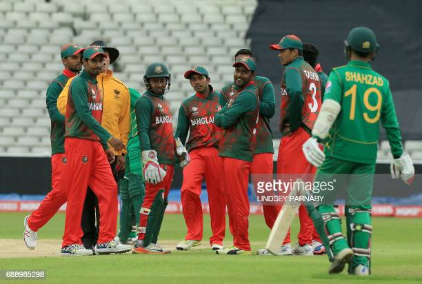 Bangladesh bowler Shakib Al Hasan celebrates with teammates as Pakistan batsman Ahmad Shahzad leaves the crease with 44 during an ICC Champions...