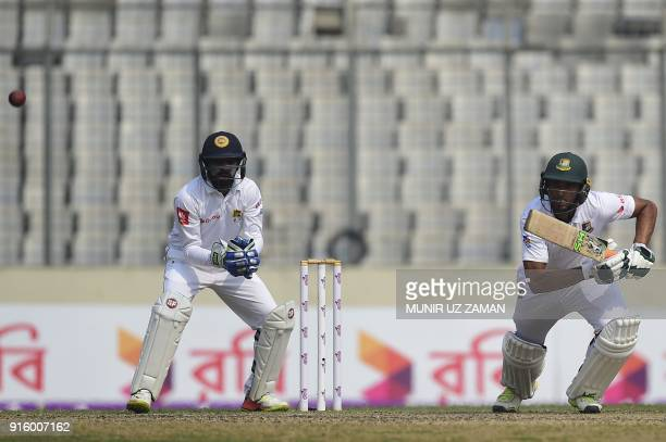 Bangladesh cricket captain Mahmudullah Riyad plays a shot as Sri Lankan wicketkeeper Niroshan Dickwella looks on during the second day of the second...