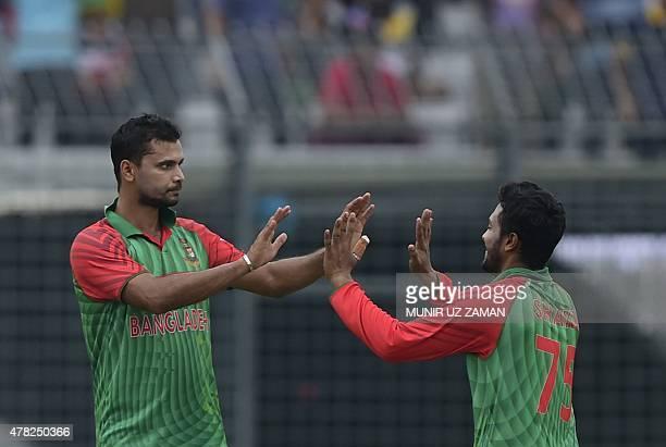 Bangladesh cricket captain Mashrafe Bin Mortaza celebrates with teammate Shakib Al Hasan after the dismissal of Indian cricketer Shikhar Dhawan...