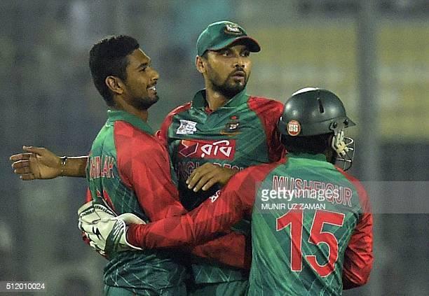 Bangladesh cricket captain Mashrafe Bin Mortaza congratulates teammate Mohammad Mahmudullah alongside wicketkeeper Mushfiqur Rahim after the...