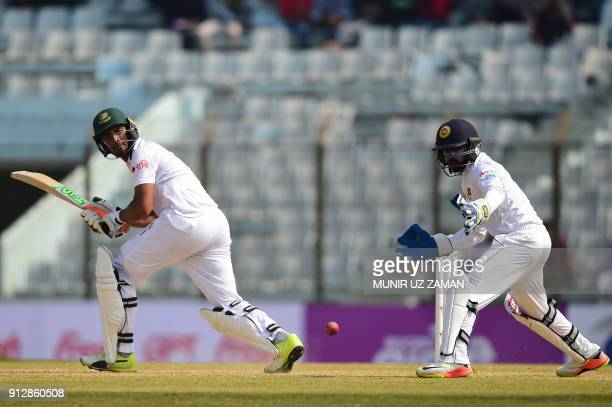 Bangladesh cricket captain Mohammad Mahmudullah plays a shot as the Sri Lanka wicketkeeper Niroshan Dickwella looks on during the second day of the...