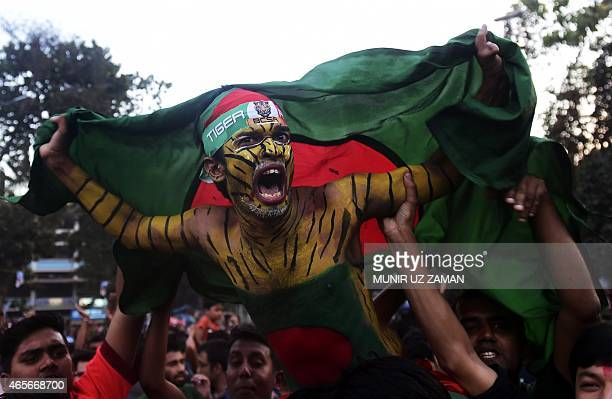 A Bangladesh cricket fan holding the national flag celebrates the national team's win against England in the ICC World Cup 2015 in Dhaka on March 9...