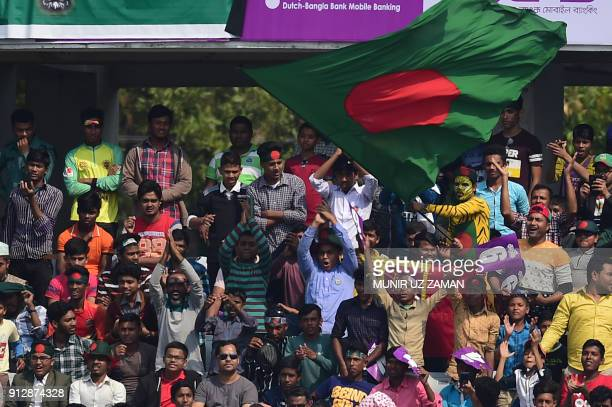 Bangladesh cricket spectators wave theg Bangladesh national flag during the second day of the first cricket Test between Bangladesh and Sri Lanka at...