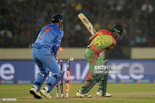 Bangladesh cricketer Anamul Haque is bowled as Indian captain Mahendra Singh Dhoni looks on during the ICC World Twenty20 tournament Group 2 cricket...
