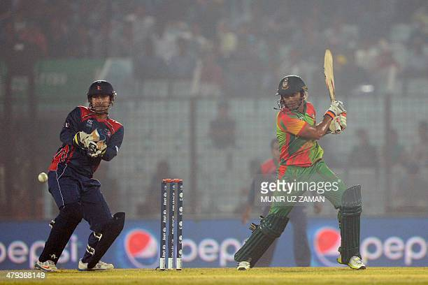 Bangladesh cricketer Anamul Haque plays a shot as the Nepal wicketkeeper Subash Khakurel looks on during the ICC Twenty20 World Cup sixth qualifying...
