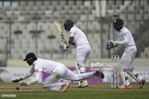 Bangladesh cricketer Liton Das plays a shot as the Sri Lanka cricketer Dhananjaya de Silva tries to catch the ball and wicketkeeper Niroshan...