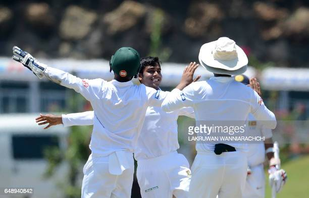 Bangladesh cricketer Mehedi Hasan celebrates the wicket of Sri Lankan cricketer Dimuth Karunaratne with teammates on the first day of the opening...