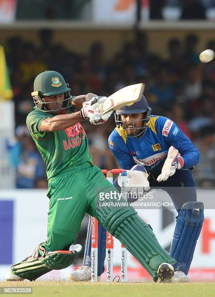 Bangladesh cricketer Mehedi Hasan is watched by Sri Lankan wicketkeeper Dinesh Chandimal as he plays a shot during the third and final one day...