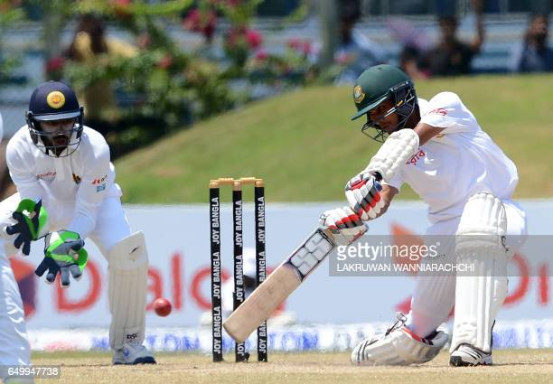 Bangladesh cricketer Mehedi Hasan plays a shot as Sri Lanka wicketkeeper Niroshan Dickwella looks on during the third day of the opening Test cricket...