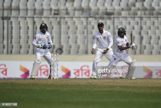 Bangladesh cricketer Mehedi Hasan plays a shot as Sri Lankan wicketkeeper Niroshan Dickwella looks on during the second day of the second cricket...