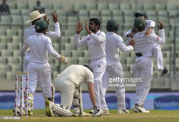 Bangladesh cricketer Mehidy Hasan celebrates with his teammates after the dismissal of the Zimbabwe cricketer Peter Moor during the fifth day of the...