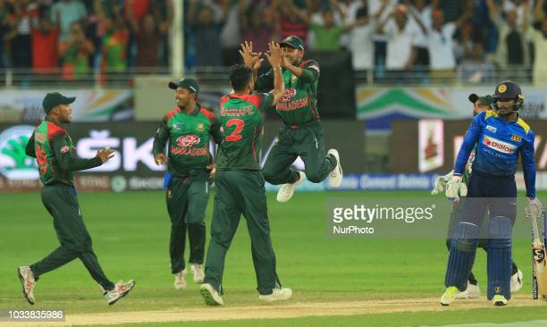 Bangladesh cricketer Mehidy Hasan leaps in the air in celebration with captain Mashrafe Mortaza and team members during the first cricket match of...