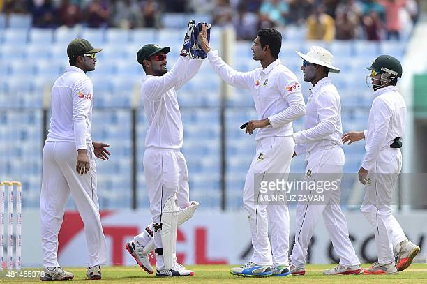 Bangladesh cricketer Mohammad Mahmudullah celebrates with teammates the wicket of South African cricketer Stiaan van Zyl during the first day of the...
