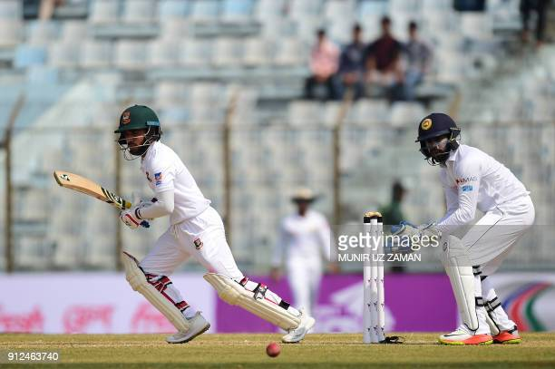 Bangladesh cricketer Mominul Haque plays a shot as the Sri Lanka wicketkeeper Niroshan Dickwella looks on during the first day of the first cricket...