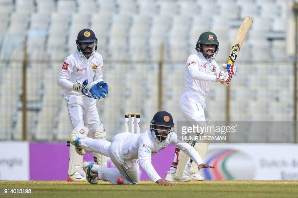 Bangladesh cricketer Mominul Haque plays a shot as the Sri Lanka cricketer Kusal Mendis tries to catch the ball and the wicketkeeper Niroshan...