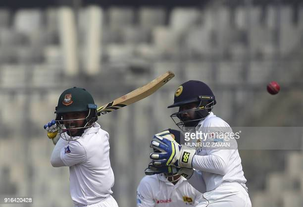Bangladesh cricketer Mominul Haque plays a shot as the Sri Lanka wicketkeeper Niroshan Dickwella looks on during the third day of the second cricket...