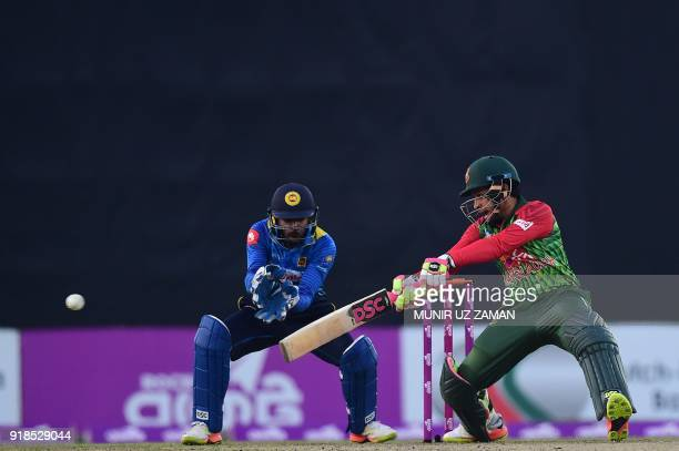 Bangladesh cricketer Mushfiqur Rahim bats as the Sri Lanka wicketkeeper Niroshan Dickwella looks on during the first Twenty20 cricket match between...