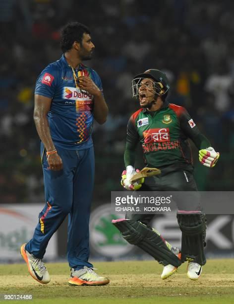 Bangladesh cricketer Mushfiqur Rahim celebrate their team's five wickets victory over Sri Lanka after as Sri Lankan cricketer Thisara Perera looks on...