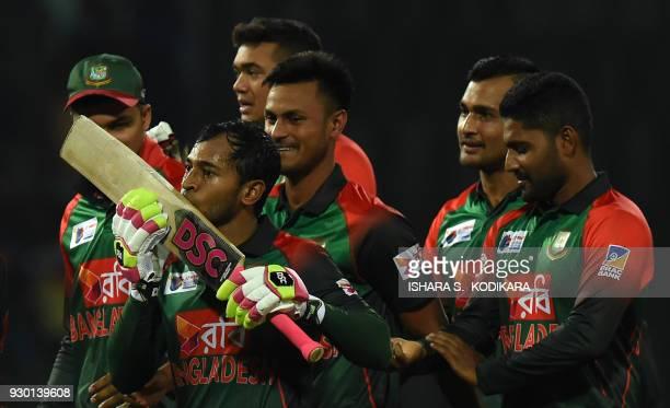 Bangladesh cricketer Mushfiqur Rahim kisses his bat as he celebrates their team's five wicket victory over Sri Lanka after the third Twenty20...