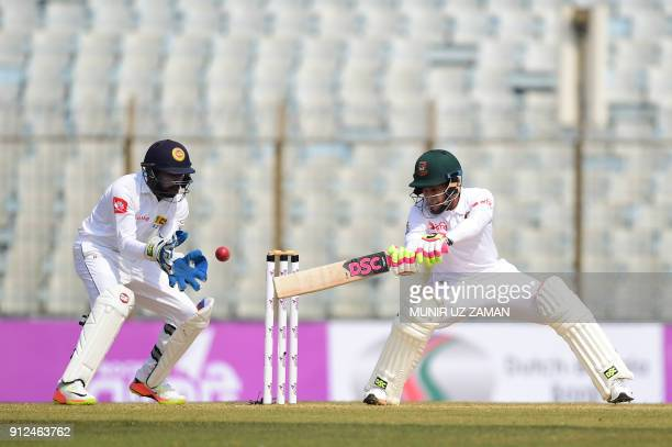 Bangladesh cricketer Mushfiqur Rahim plays a shot as the Sri Lanka wicketkeeper Niroshan Dickwella looks on during the first day of the first cricket...