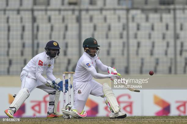 Bangladesh cricketer Mushfiqur Rahim plays a shot as the Sri Lanka wicketkeeper Niroshan Dickwella looks on during the third day of the second...