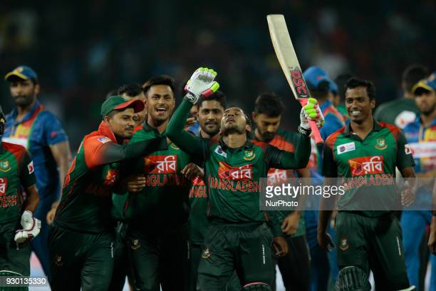 Bangladesh cricketer Mushfiqur Rahim reacts hugged is accompanied by his team mates after scoring the winning runs during the 3rd T20 cricket match...