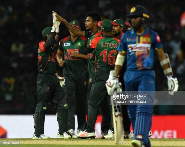 Bangladesh cricketer Mustafizur Rahman celebrates with his teammates after he dismissed Sri Lankan cricketer Danushka Gunathilaka during the third...