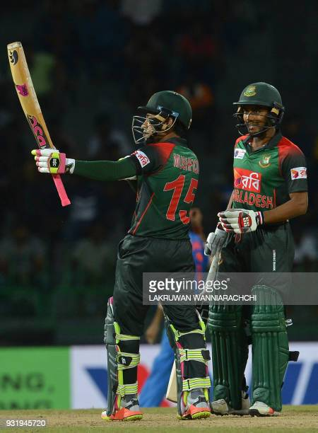 Bangladesh cricketer Mustafizur Rahman is watched by his teammate Sabbir Rahman as he raises his bat to the crowd after scoring a halfcentury during...