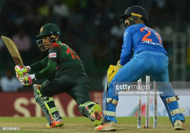 Bangladesh cricketer Mustafizur Rahman is watched by Indian wicketkeeper Dinesh Karthik as he plays a shot during the fifth Twenty20 international...
