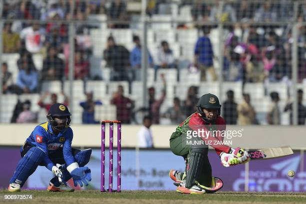 Bangladesh cricketer Mustafizur Rahman plays a shot as the Sri Lanka cricketer Niroshan Dickwella looks on during the third one day international...
