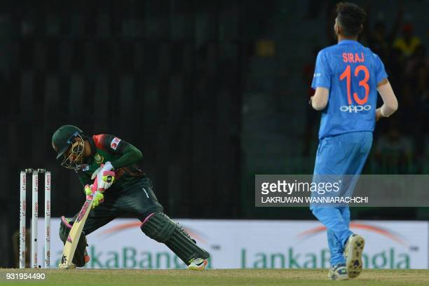 Bangladesh cricketer Mustafizur Rahman reacts after losing to India by 17 runs as Indian cricketer Mohammed Siraj runs next to him during the Fifth...