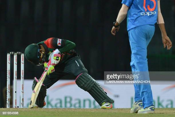 Bangladesh cricketer Mustafizur Rahman reacts after losing to India by 17 runs as Indian cricketer Mohammed Siraj walks next to him during the Fifth...