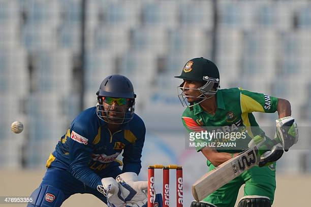 Bangladesh cricketer Nasir Hossain plays a shot as Sri Lankan wicketkeeper Kumar Sangakkara looks on during the tenth match of the Asia Cup oneday...