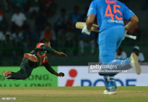 Bangladesh cricketer Nazmul Islam dives as he attempts to field a ball hit by Indian cricketer Rohit Sharma during the fifth Twenty20 international...