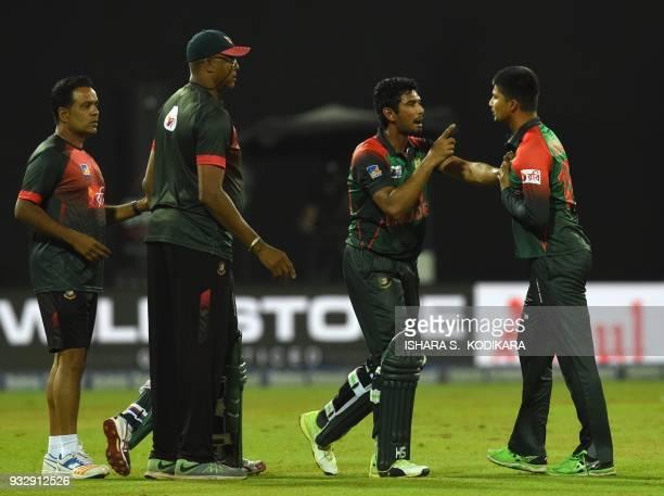 Bangladesh cricketer Nurul Hasan exchanges words with Bangladesh cricketer Mahmudull as coach Courtney Walsh looks on during the sixth Twenty20...