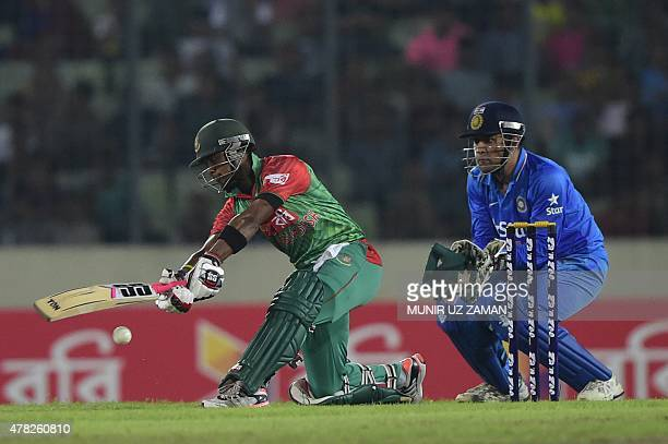 Bangladesh cricketer Sabbir Rahman plays a shot as Indian cricket captain Mahendra Singh Dhoni looks on during the third ODI cricket match between...