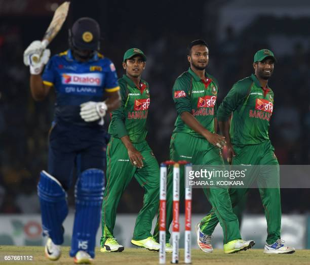 Bangladesh cricketer Shakib Al Hasan celebrates with teammates after he dismissed Sri Lankan cricketer Asela Gunaratne during the first one day...