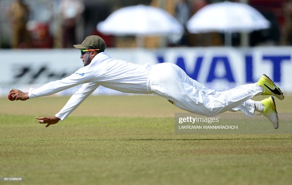TOPSHOT - Bangladesh cricketer Shakib Al Hasan dives as he attempts to field a ball hit by Sri Lankan cricketer Upul Tharanga during the fourth day of their opening Test match between Sri Lanka and Bangladesh at the Galle International Cricket Stadium in Galle on March 10, 2017. /