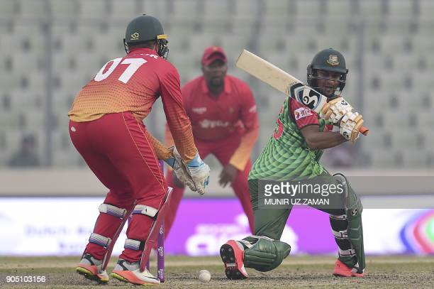 Bangladesh cricketer Shakib Al Hasan palys a shot as the Zimbabwe wicketkeeper Brendan Taylor looks on during the first One Day International cricket...