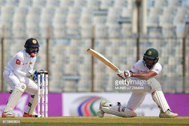 Bangladesh cricketer Sunzamul Islam plays a shot as the Sri Lanka wicketkeeper Niroshan Dickwella looks on during the second day of the first cricket...
