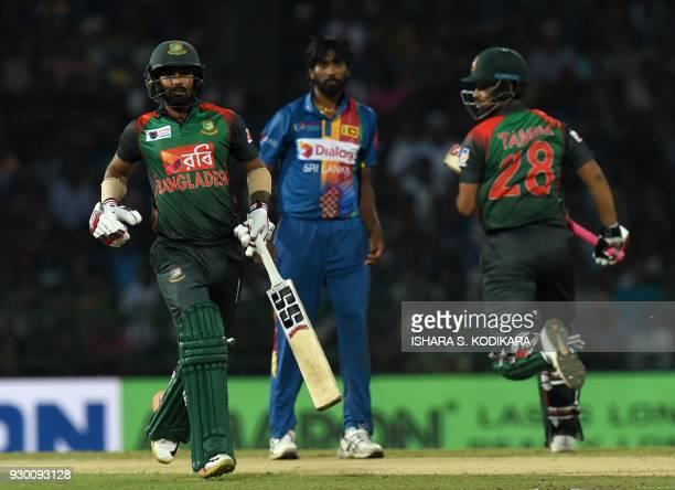 Bangladesh cricketer Tamim Iqbal and Liton Das runs between the wickets as Sri Lankan cricketer Nuwan Pradeep looks on during the third Twenty20...