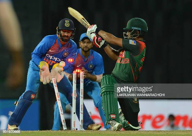 Bangladesh cricketer Tamim Iqbal gets dismissed by Indian cricketer Washington Sundar as wicketkeeper Dinesh Karthik and Suresh Raina look on during...