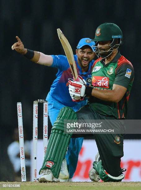 Bangladesh cricketer Tamim Iqbal gets dismissed by Indian cricketer Washington Sundar Indian cricketer Suresh Raina look on during the fifth Twenty20...